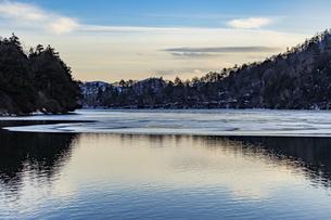 夕焼けに染まる空を映し出す真冬の湖面の写真素材 [FYI04743262]