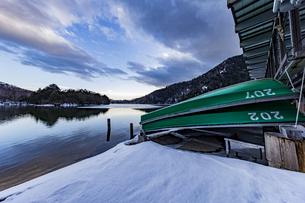 夕暮れ時の冬の静かな湯ノ湖とボートの写真素材 [FYI04743268]