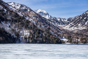 湯ノ湖を囲む山々と凍結した湖面の写真素材 [FYI04743282]