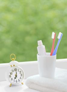 窓辺の歯ブラシと時計とタオルの写真素材 [FYI04744355]