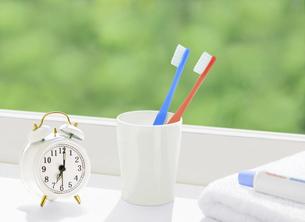 窓辺の歯ブラシと時計とタオルの写真素材 [FYI04744358]