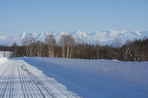 冬の道路と青空と山並みの写真素材 [FYI04744462]