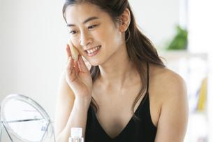 頬にパフをあて化粧をする女性の写真素材 [FYI04744548]
