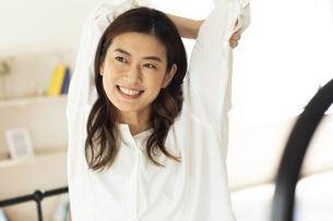 ベッドの上でストレッチをする笑顔の女性の写真素材 [FYI04744559]