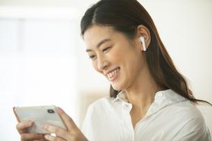部屋でスマートフォンを操作するイヤホンをした女性の写真素材 [FYI04744560]
