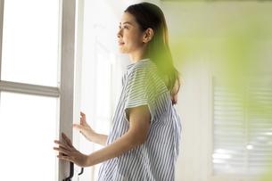 窓際で窓の外を見つめる女性の写真素材 [FYI04744570]