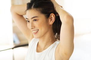 部屋で髪の毛を結ぶ笑顔の女性の写真素材 [FYI04744578]