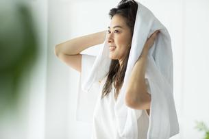 窓際で髪の毛をタオルドライする女性の写真素材 [FYI04744594]