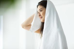 窓際で髪の毛をタオルドライする女性の写真素材 [FYI04744595]