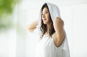 窓際で髪の毛をタオルドライする女性の写真素材 [FYI04744596]