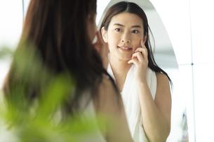 鏡の前で頬に手を当てるお風呂上がりの女性の写真素材 [FYI04744599]