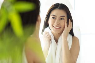 鏡の前で頬に手を当てるお風呂上がりの女性の写真素材 [FYI04744600]