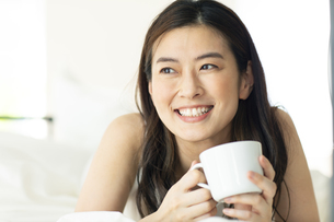 ベッドに横たわりマグカップを持つ女性の写真素材 [FYI04744635]