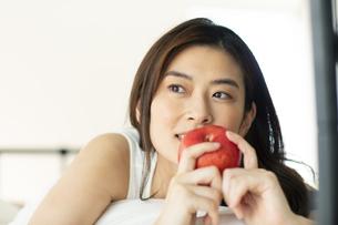 ベッドに横たわり果物を持つ女性の写真素材 [FYI04744636]