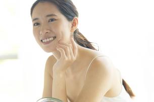 鏡の前で頬に手を添える女性の写真素材 [FYI04744678]