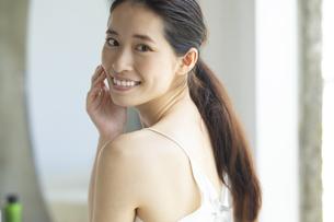 顔に手を添えながら振り向く笑顔の女性の写真素材 [FYI04744679]