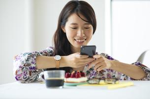 スマートフォンでケーキの写真を撮る女性の写真素材 [FYI04744687]