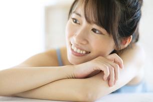 机の上に伏せる笑顔の女性の写真素材 [FYI04744694]