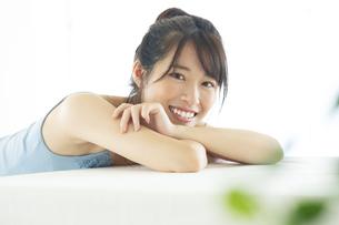 机の上に伏せる笑顔の女性の写真素材 [FYI04744700]