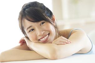 机の上に伏せる笑顔の女性の写真素材 [FYI04744701]