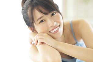 机の上に伏せる笑顔の女性の写真素材 [FYI04744702]