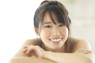 机の上に伏せる笑顔の女性の写真素材 [FYI04744704]