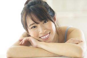 机の上に伏せる笑顔の女性の写真素材 [FYI04744705]