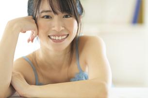 机の上に伏せる笑顔の女性の写真素材 [FYI04744707]