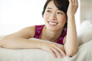 ベッドに横たわる笑顔の女性の写真素材 [FYI04744713]