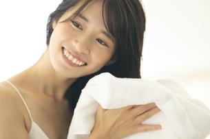 部屋で髪の毛をタオルドライする女性の写真素材 [FYI04744718]