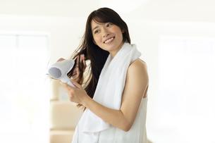 部屋で髪の毛をドライヤーで乾かす笑顔の女性の写真素材 [FYI04744723]