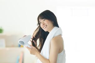 部屋で髪の毛をドライヤーで乾かす笑顔の女性の写真素材 [FYI04744724]