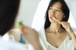 お風呂上がりに鏡の前で歯磨きをする女性の写真素材 [FYI04744727]