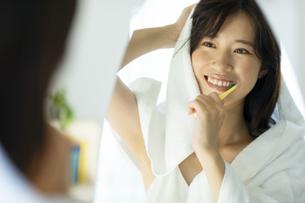 お風呂上がりに鏡の前で歯磨きをする女性の写真素材 [FYI04744728]