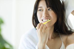 お風呂上がりに鏡の前で歯磨きをする女性の写真素材 [FYI04744729]