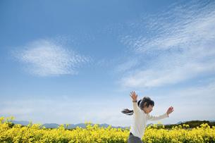 菜の花畑を駆け抜ける女の子の写真素材 [FYI04745926]
