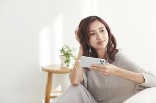 ソファに座りスマホを見る若い日本人女性 の写真素材 [FYI04747011]