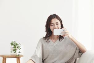 ソファに座りスマホを見る若い日本人女性 の写真素材 [FYI04747013]