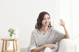 ソファに座りスマホを見る若い日本人女性 の写真素材 [FYI04747029]