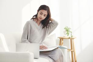ソファに座りノートパソコンを使う若い日本人女性 の写真素材 [FYI04747031]
