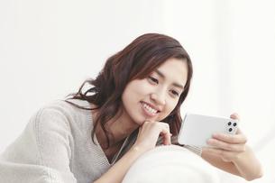 ソファに座りスマホを見る若い日本人女性 の写真素材 [FYI04747036]