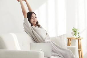 ソファに座りノートパソコンを使う若い日本人女性の写真素材 [FYI04747037]