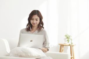ソファに座りノートパソコンを使う若い日本人女性 の写真素材 [FYI04747042]