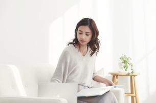 ソファに座りノートパソコンを使う若い日本人女性の写真素材 [FYI04747172]