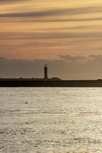 夕焼けのオレンジ色の空にシルエットが映し出される釧路港の灯台の写真素材 [FYI04747243]