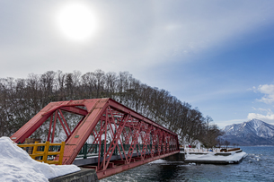 支笏湖に架かる道内最古の山線鉄橋と太陽の写真素材 [FYI04747375]