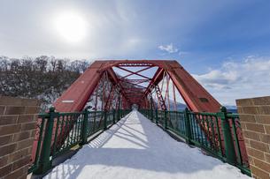 支笏湖に架かる道内最古の山線鉄橋と太陽の写真素材 [FYI04747377]