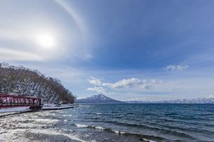 支笏湖に架かる道内最古の山線鉄橋と太陽の写真素材 [FYI04747379]