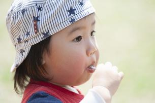 飴を頬張る幼児の写真素材 [FYI04747484]