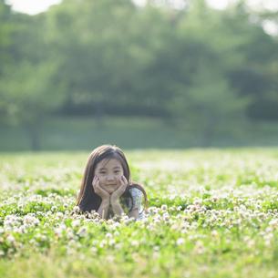 シロツメクサの花畑で頬杖をつく女の子の写真素材 [FYI04747552]